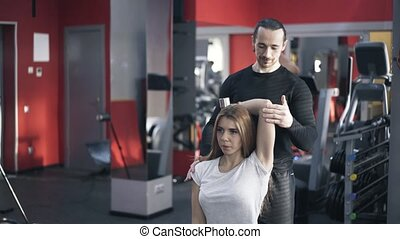 Trainer helping woman to do a dumbbell exercise
