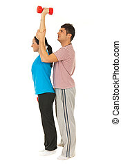 Trainer helping woman to doing exercises