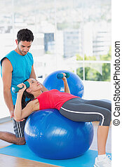 Trainer helping woman with her exercises at gym
