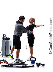 Trainer helps attaching ems - Trainer helps woman attaching...