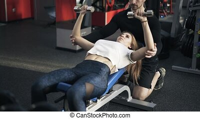 Trainer is monitoring a woman doing a dumbbell exercise on bench, tilt up