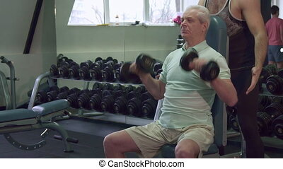 Trainer keeps his hands on the elbows of senior client
