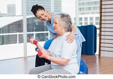 Trainer looking at senior woman lifting dumbbells