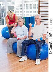 Trainer motivating senior couple in lifting dumbbells