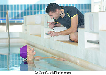 trainer showing cronometer at a swimmer at the pool