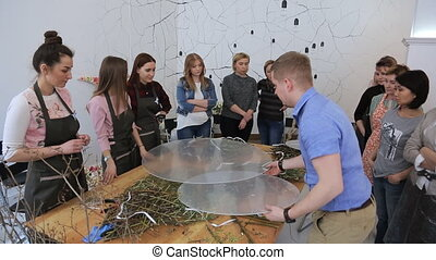 Trainer shows to group of women creative composition in art studio