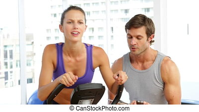 Trainer timing his client on exercise bike at the gym