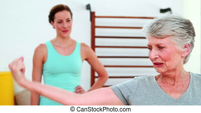 Trainer watching proud elderly client flexing her bicep at...