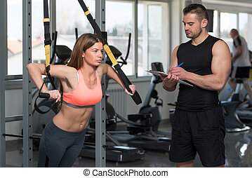 Trainer With Clipboard Woman On Trx Fitness Straps -...