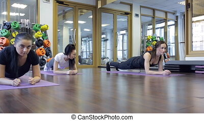 Trainer with her group of women stand pose of plank on mat in gym.