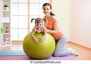 Trainer with kid doing fitness on ball