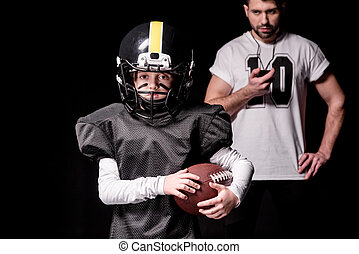 Trainer with sport timer looking at boy american football player