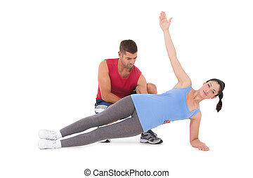 Trainer with woman in plank position