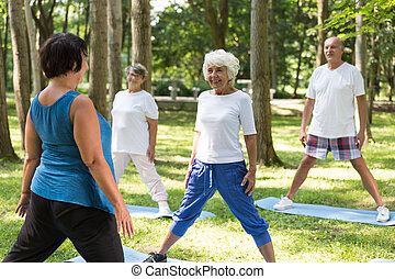 Trainer working out with seniors outdoor