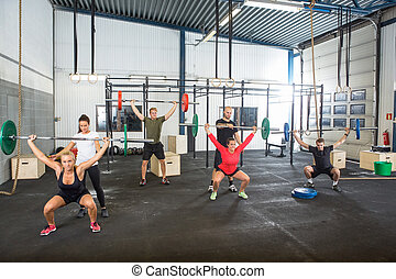 Crossfit trainers assisting athletes in exercising with barbells at gym