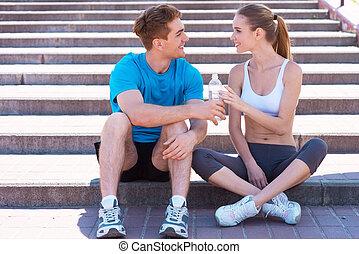 trainieren, zusammen, gleichfalls, fun., seitenansicht, von, schöne , junges, in, sportarten-kleidung, sitzen treppe, voreinander, und, lächeln