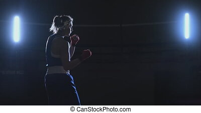 Training a beautiful female boxer doing punches in a dark room. Steadicam shot. Preparation for self-defense and fight in the ring.