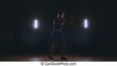 Training a beautiful female boxer doing punches in a dark...