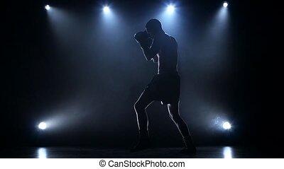 Training a blow boxer. Dark studio with spotlights -...