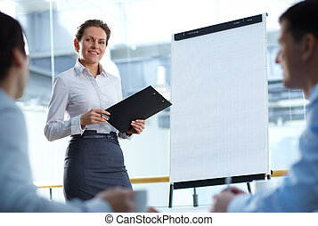 Training - A businesswoman standing by whiteboard and...