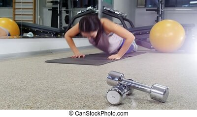 Training. A young woman doing push ups. Dumbbells on the...
