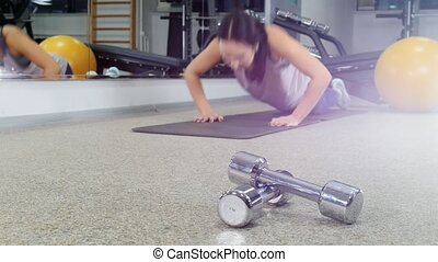 Training. A young woman doing push ups in the gym. Dumbbells on the foreground