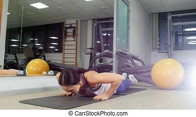 Training. A young woman doing push ups. Mid shot