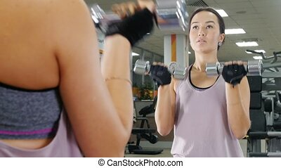 Training. A young woman pumps her hand muscles with a dumbbells. Looking in the mirror