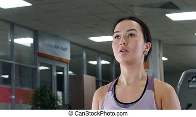 Training. A young woman pumps her hand muscles with a dumbbells. Looking in the mirror. Portrait