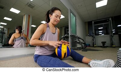 Training. A young woman sitting on the floor and playing with ball. Slow motion