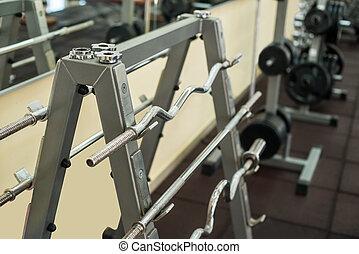 Training apparatus in gym. Barbells hanging on metal rack in...