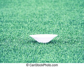 Training cone for football on a green field. Artificial green turf