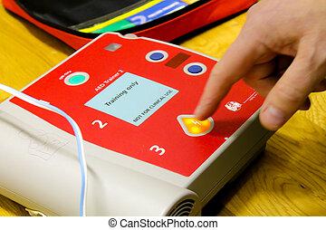 Training defibrillator - A finger pressing a button of a...