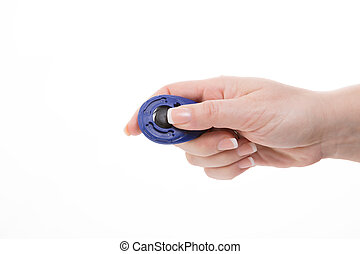 female hand holding a clicker for training cats and dogs