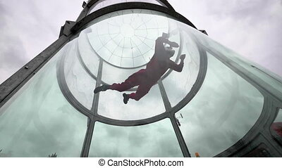 Training flight young woman skydiver in a wind tunnel....