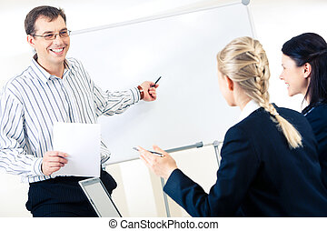 Training - Friendly man standing at whiteboard and pointing...