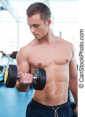Training his muscles. Confident young muscular man training with dumbbell while standing in gym