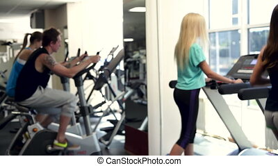 People training in a gym using treadmills and exercise bicycles.