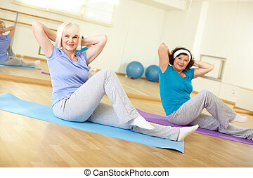 Training in gym - Portrait of sporty females doing physical ...