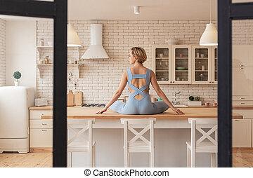 Skinny blonde woman sitting on table in lotus pose