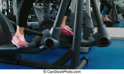 Training in the gym on the elliptical trainer feet