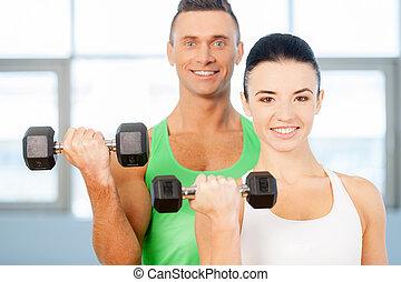 training, mit, dumbbells., paar, heben, hanteln, in, a, turnhalle, und, lächeln, kamera