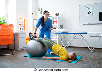 Professional dark-haired therapist helping little girl with stretching