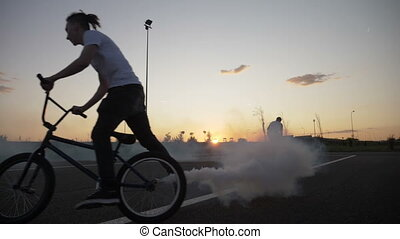 Training of young bikers riding and practicing acrobatic techniques on cycling circuit outdoor at the sunset with smoke