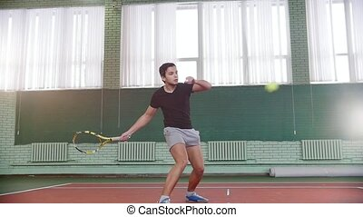 Training on the tennis court. Young man playing tennis