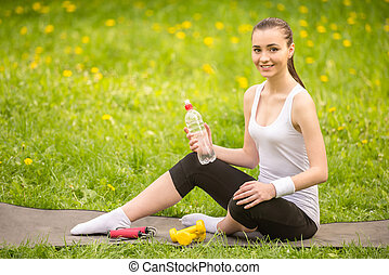 Training outdoors - Beautiful sporty girl sitting on the mat...
