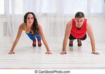 Training. Sportive girl and guy workout together making push...