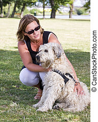 Woman sitting down, correcting a dog, outdoors in a park.