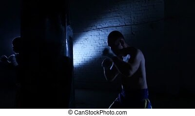 Training with a punching bag in a boxing club. Slow motion.