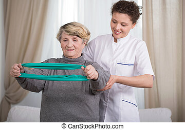 Training with exercise elastic band - Active elder lady...